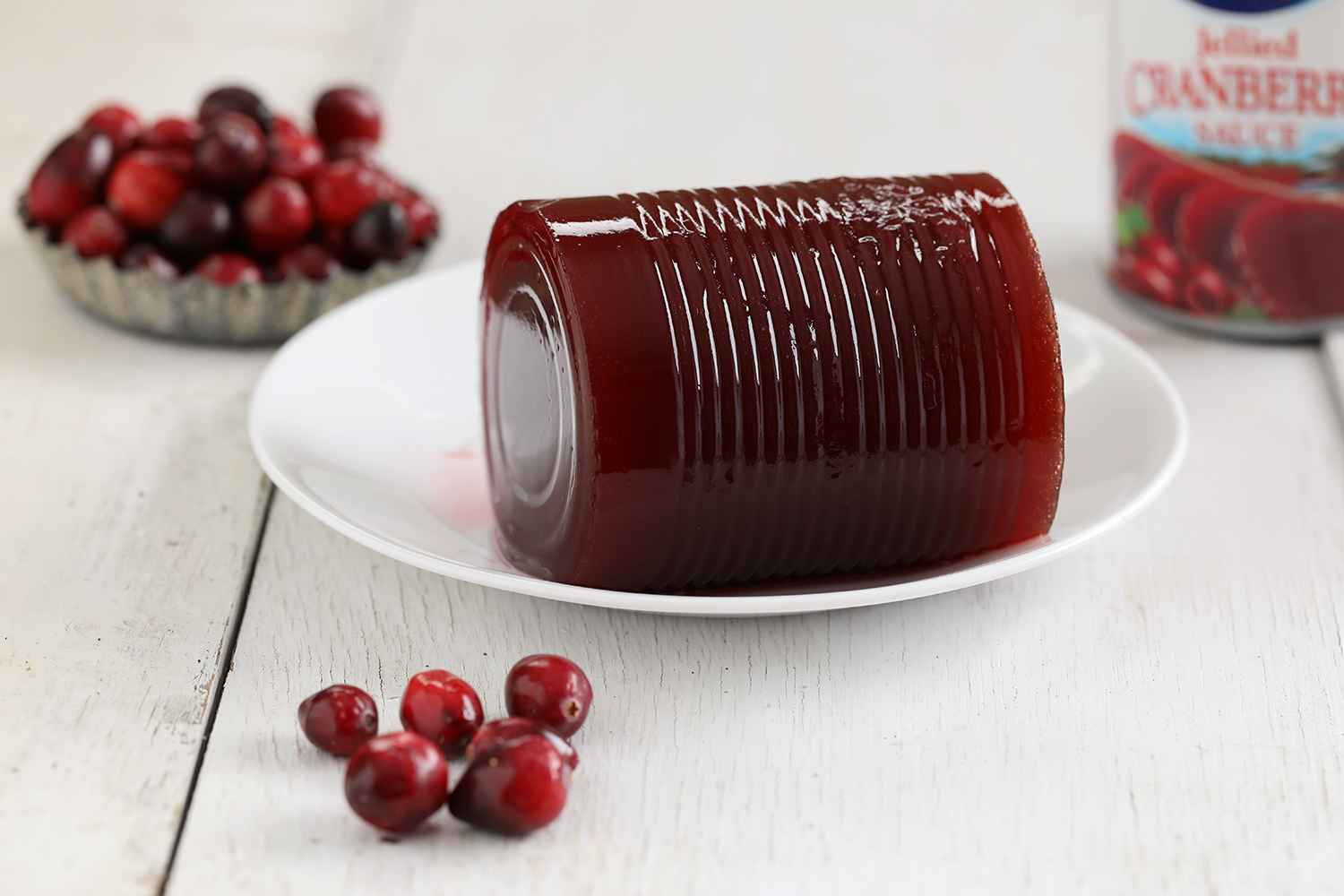 Red cranberry jelly from a can sitting upon a white place surrounded by cranberries.
