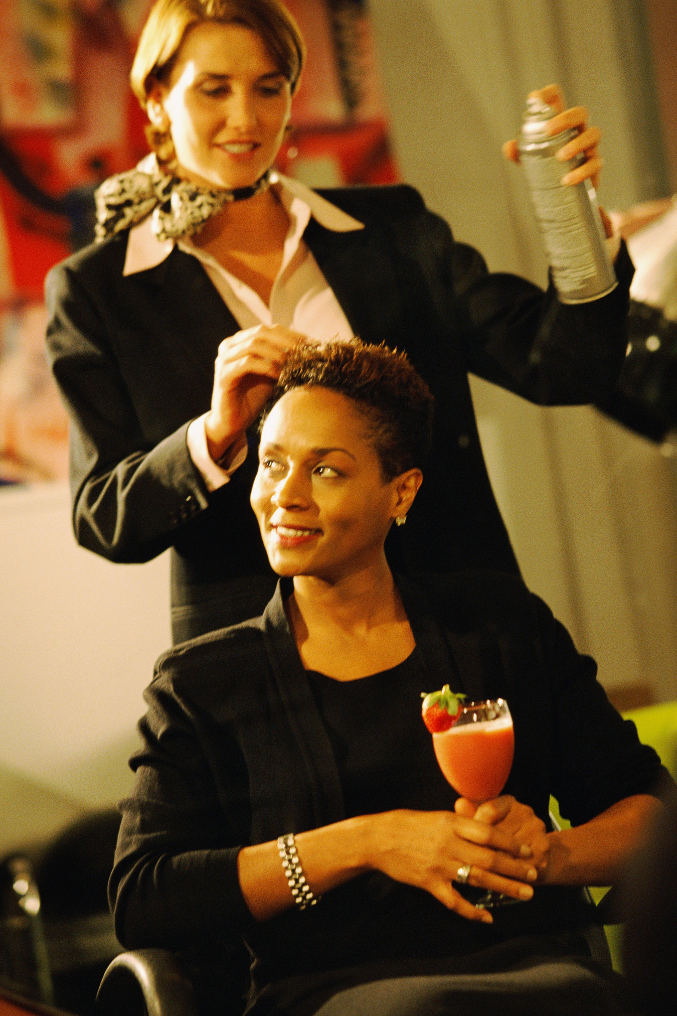 Woman getting her hair styled by another woman