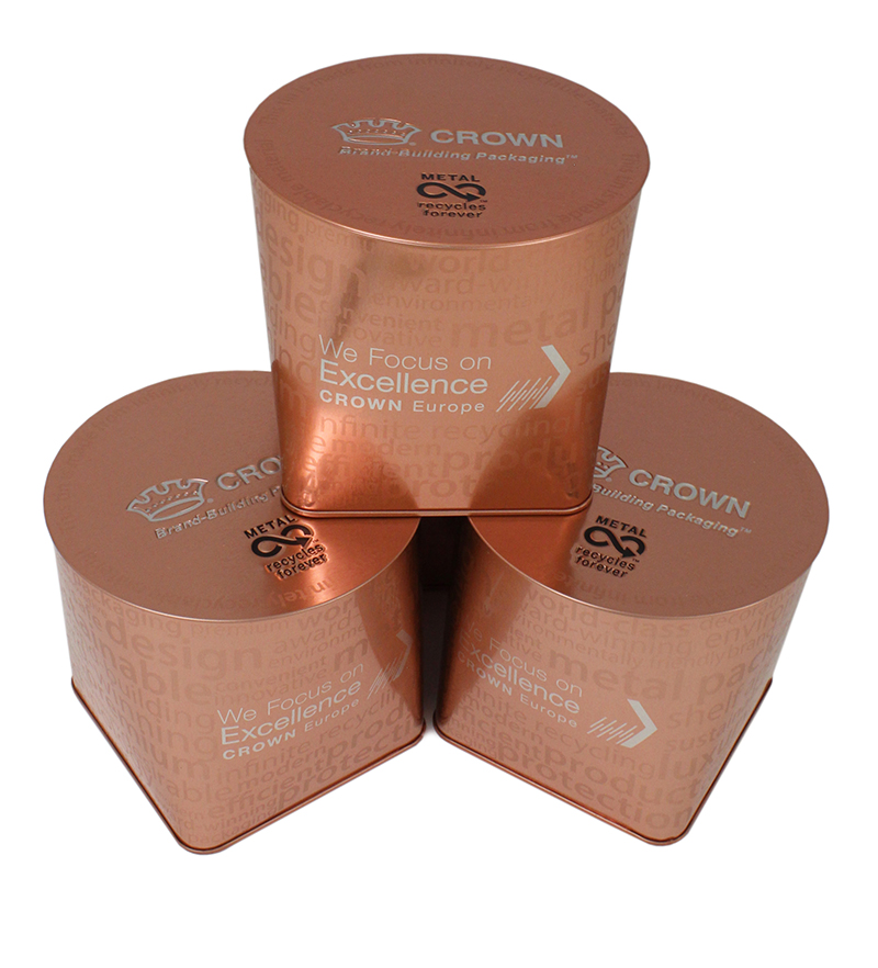 Three bronze tins stacked on top of one another.