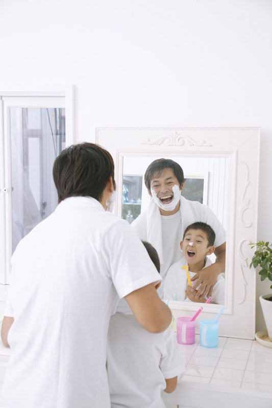 Father and son looking in the mirror and shaving