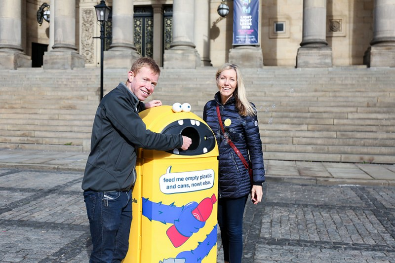 Two people standing next to a yellow garbage can.
