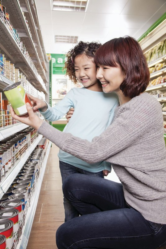 Woman and girl selecting a can of food