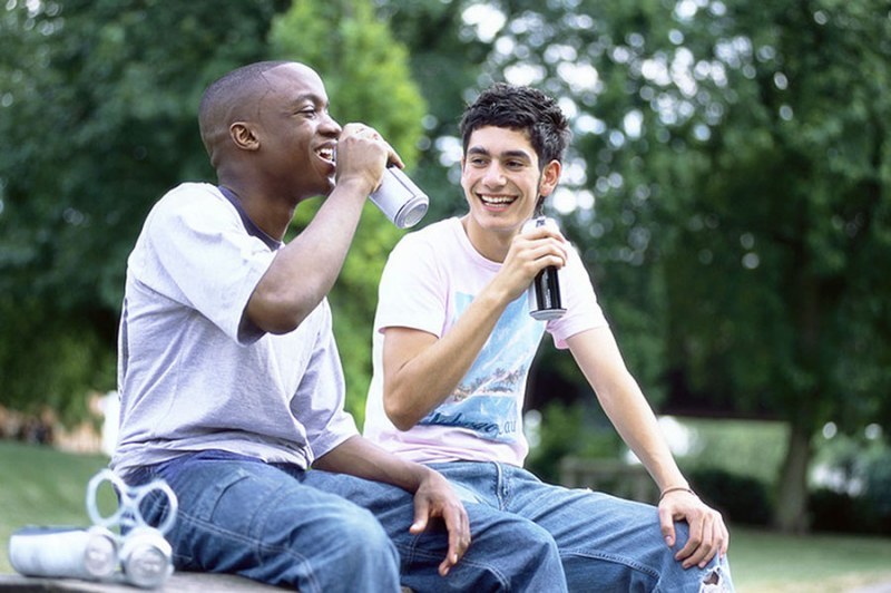 Two teenagers sitting and drinking from beverage cans