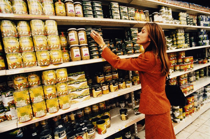 Women shopping in a grocery store looking at canned goods
