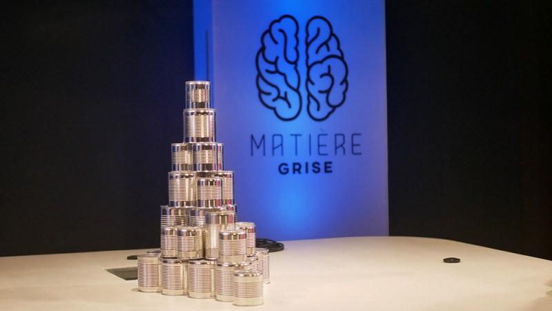 Silver cans stacked in a pyramid next to a sign that says, Matiere Grise.
