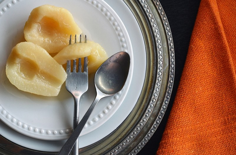 Sliced pears on a white plate with a fork and spoon next it them.
