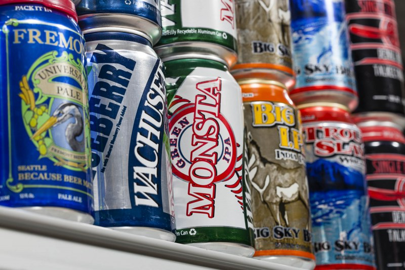 A shelf of various beer cans